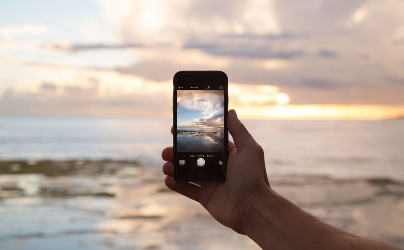 Taking a photo of a sunset using a smartphone